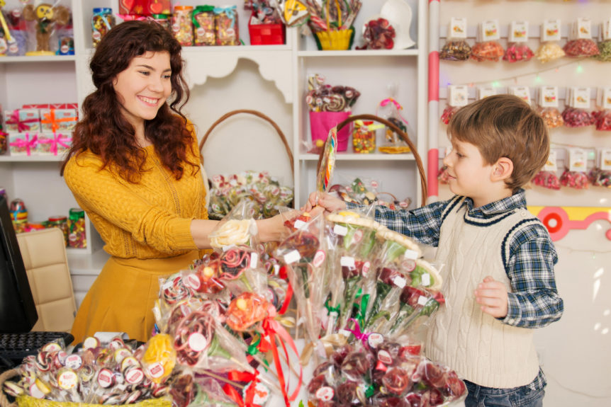 Happy boy buying sweets in the store. Beautiful woman salesman gives candies to boy